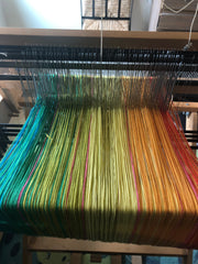 warp yarns threaded through a loom, in a rainbow of colors