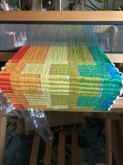 weaving in progress on a loom, with a block pattern in a rainbow sequence