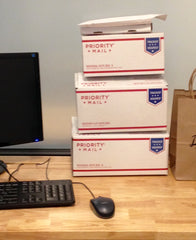 USPS shipping boxes stacked on a desktop next to a computer