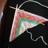 knitting in progress, with rainbow-striped yarn in a triangle shape, with bamboo needles