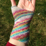 a finished handspun mitt in rainbow yarn, being modeled on a hand, palm up