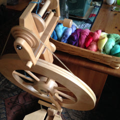 view of a Lendrum spinning wheel from above, with a basket of rainbow-dyed yarn on a table behind