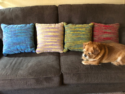 four colorful handwoven cushions on a grey sofa, with a sweet tan dog resting beside them.