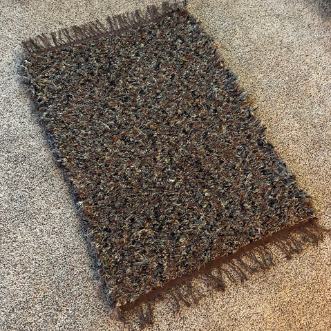 finished rag-rug in shades of brown and black, lying on a carpeted floor