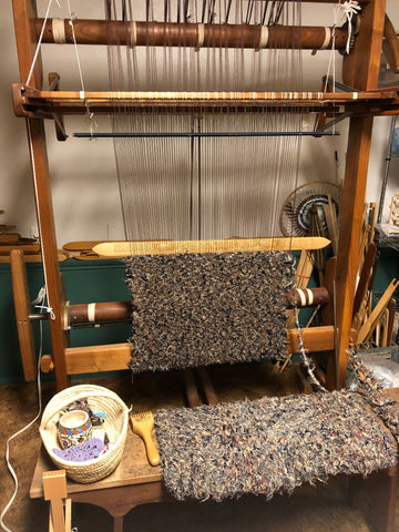 upright rug loom with partially finished rag rug and carved shed stick in place