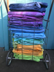 cart full of folded, dyed sheets in a cool rainbow of colors