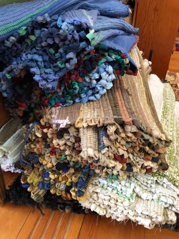 tall stack of woven rag rugs in an assortment of colors