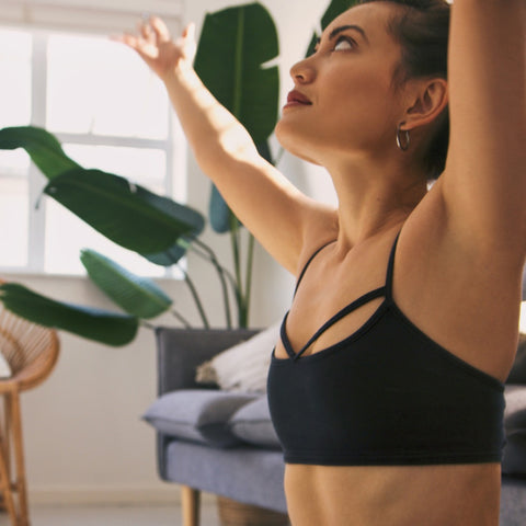 woman lifting her arms up and stretching in a yoga studio