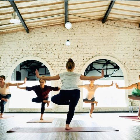 women doing a hamstring stretch in a yoga class