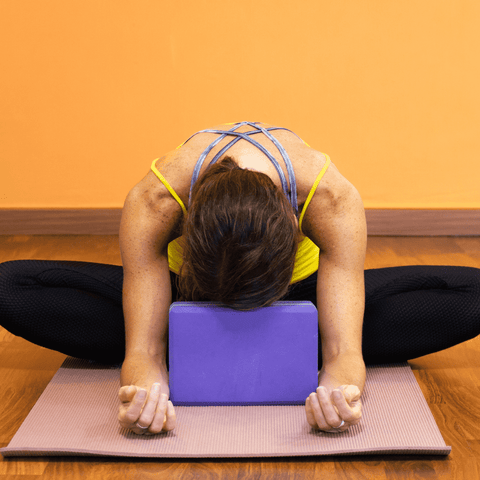 woman in a yin pose on a yoga mat