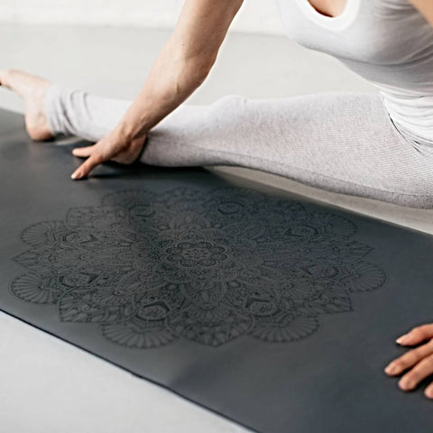 woman stretching her hamstrings on a grey yoga mat