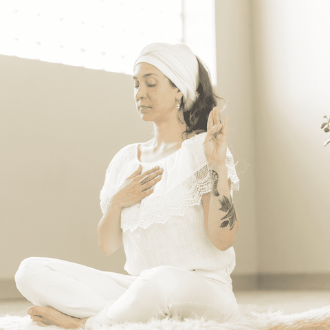 woman dressed in white meditating