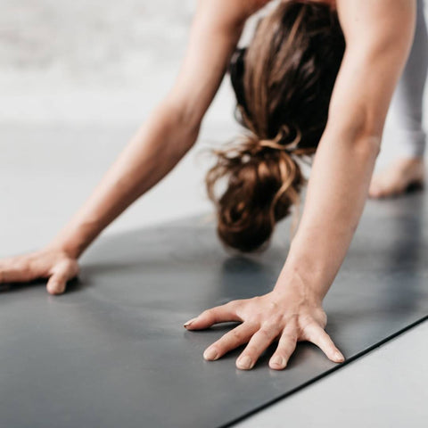 woman in downward dog pose on a grey yoga mat