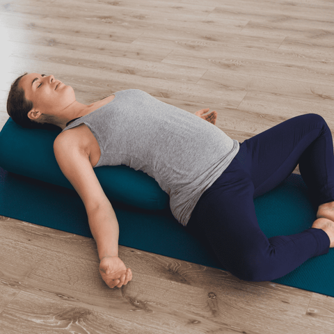 woman lying down on a yoga mat with her back on a bolster