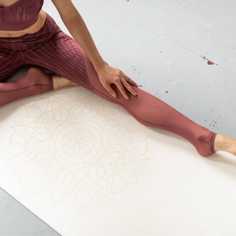 woman stretching on a white yoga mat