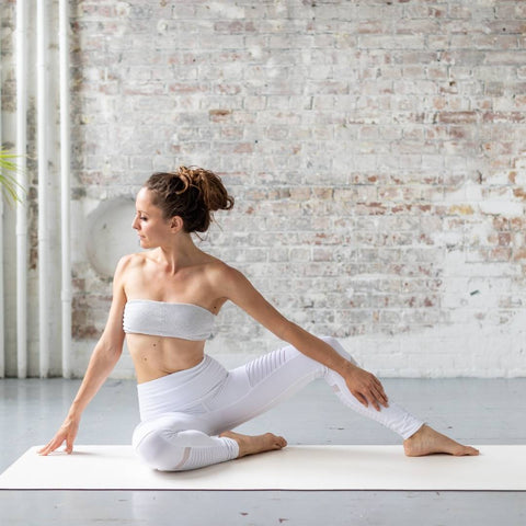 woman dressed in white stretching on a white yoga mat