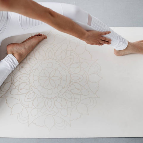 person stretching on a white yoga mat