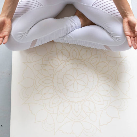 woman in lotus pose on a white yoga mat with a mandala pattern on it