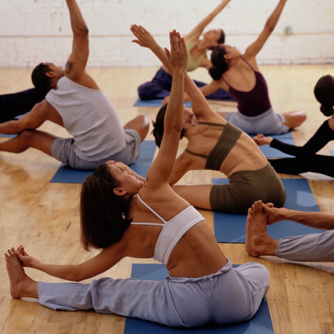 people stretching on yoga mats in a class