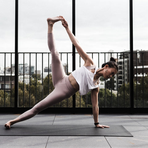 girl stretching on a black yoga mat on a balcony