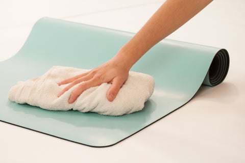Cleaning a blue DIYogi premium yoga mat with a cloth