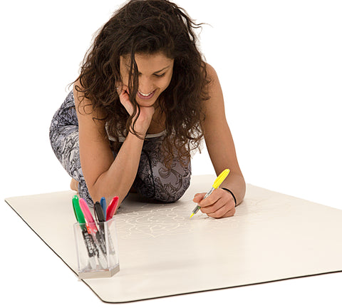 Girl drawing on a DIYogi Mandala yoga mat with a marker. The yoga mat has a Mandala engraved on it that she is colouring into.