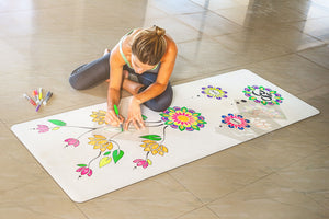 A white yoga mat with a woman drawing a mandala on it using markers.