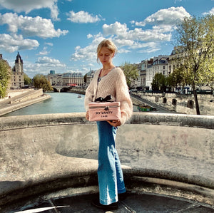 A girl in paris holding a pink beauty box for makeup necessities.
