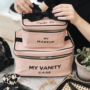"Two travel makeup cases in pink with ""my vanity case"" and ""my makeup"" printed across the front in black letters."
