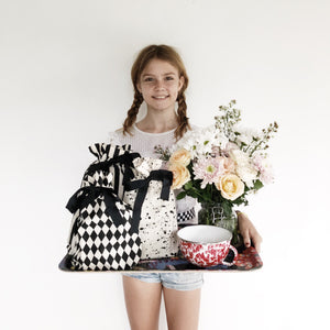A girl holding a tray with coffee, flowers and many reusable gift bags holding multiple gifts.