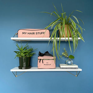 2 shelves with books and plants with a pink makeup box and a hair stuff case.