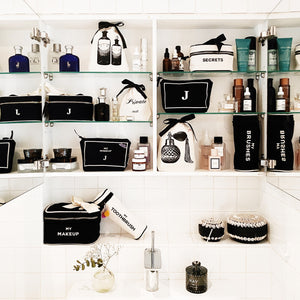A bathroom mirror display of skincare products and bathroom organizers, hairbrush cases, makeup cases and more.