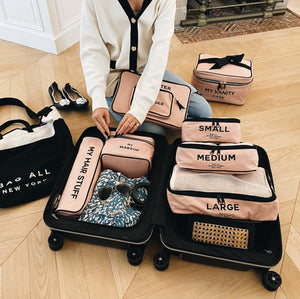 A girl packing a suitcase with all pink products, packing cubes, hair stuff case, makeup case and a computer case.