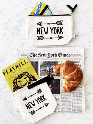 New York arrow case next to the new york times and a croissant.
