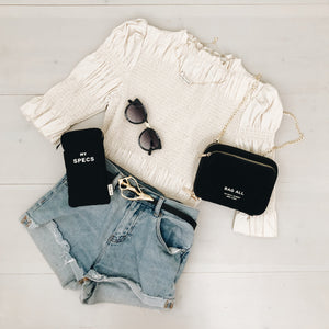 An outfit laid out that includes denim shorts, a black belt, a white top, a small organizing purse, chanel sunglasses amd a sunglasses case.