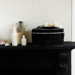 Large black blank beauty box with white details on top of a shelf.