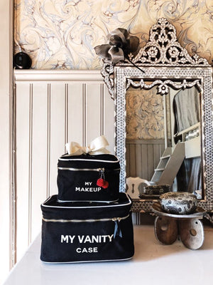"Two makeup organizer boxes on a vanity with ""my vanity case"" and ""my makeup"" across the top."