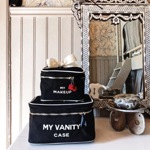 A vanity with a train case and a makeup box on the table.