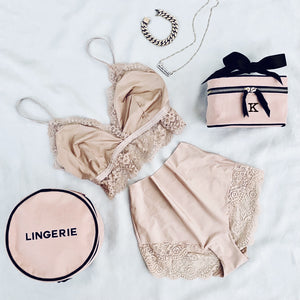 Pink lace lingerie and a gold chain bracelet with a mini pink beauty box and a pink round lingerie case.