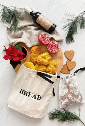 "Cream bag with a black bow and ""bread"" written across the front."