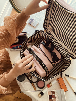A woman opening the makeup case showing the striped and lined interior as she puts her makeup away.