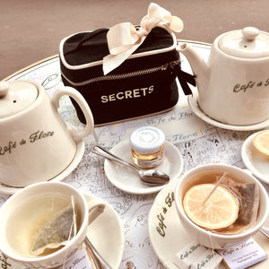 A coffe shop table with coffee and tea with a mini secrets beauty box on the table.