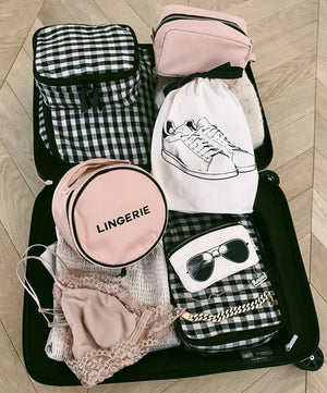 A suitcase with checkered packing cubes, a white sneaker shoe bag, sunglasses case a pink roud lingerie.