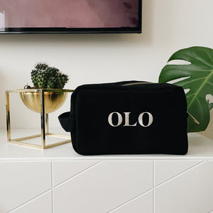 "Toiletry souki case surrounded by plants and ""OLO"" monogrammed on  it."