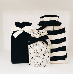Three reusable gift bags in the patterns splatter, striped and black.