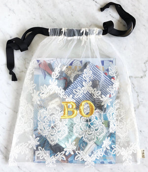 "White lace bag with necessities and a Vogue magazine with ""BO"" monogrammed on the front."