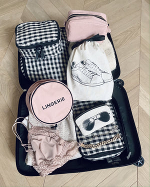 Suitcase being packed with pink bag all products and linen.