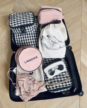 A suitcase with linen packing cubes, lingerie, white snekaers and a pink toiletry case.