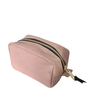 Pink toiletry case with gold zipper for travel.