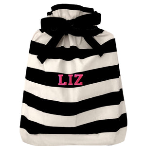 "A large reusable gift bag with black and white horizontal striped with ""LIZ"" monogrammed on the front."